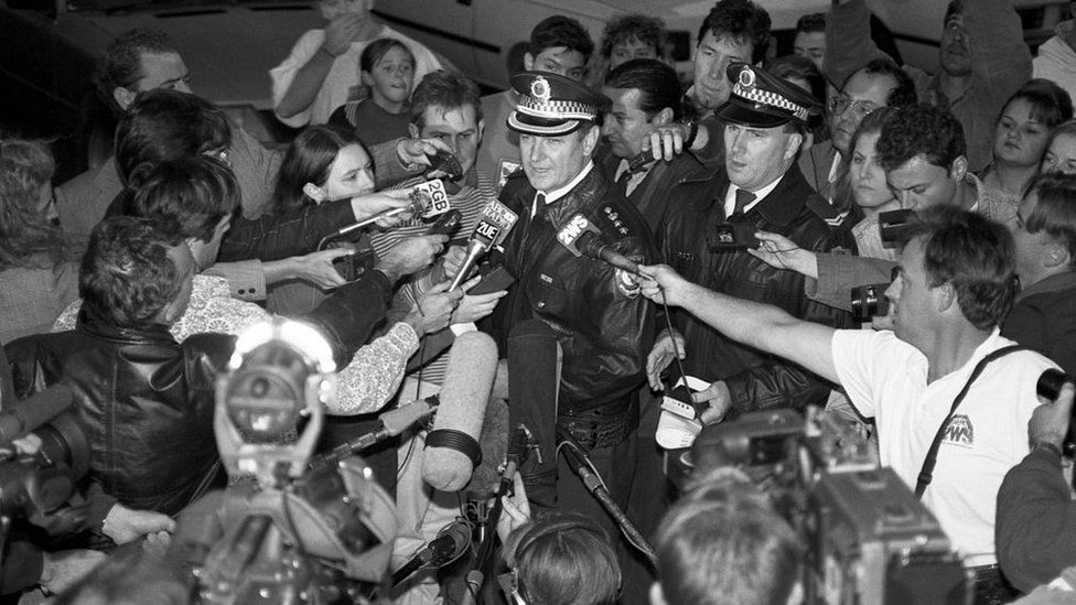 A black and white picture of a police officer giving a press conference with dozens of broadcast journalists surrounding him