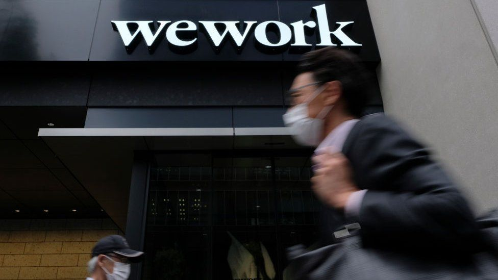 A man walks past the logo of WeWork in Tokyo on May 18, 2020.