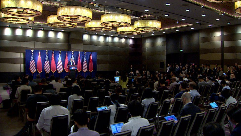 Wide shot of John Kerry talking to a room full of reporters in China.