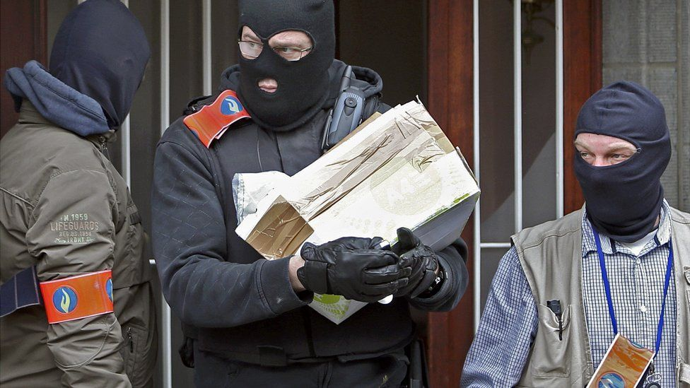 Masked Belgian police remove a package from a building in Anderlecht during searches following the attacks in Brussels - 23 March 2016