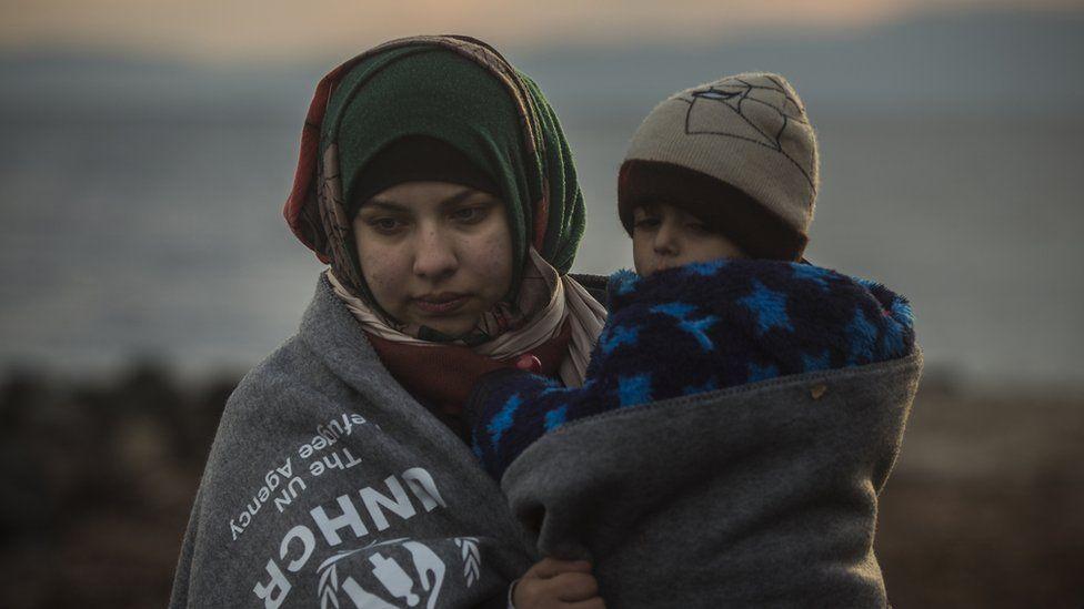 A migrant woman holds a child on a beach near the town of Mytilene