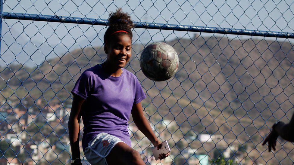 Thaissa controls the ball with a solo kick, in front of a chain-link fence through which the grassy hills beyond the favela can be seen