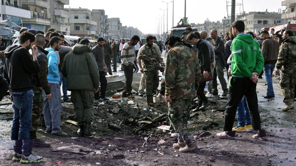 Syrians look at a crater caused by a bombing in Syria