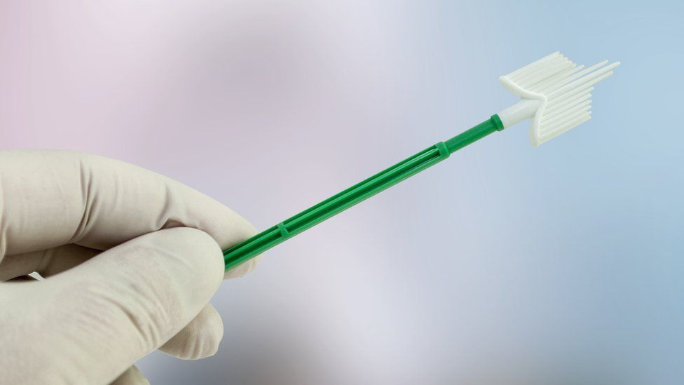 A gloved hand holding a gynaecological swab used in a smear test