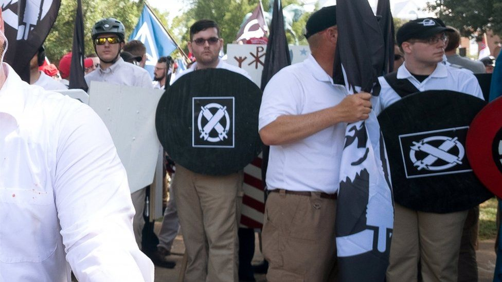 James Fields is pictured holding up a homemade shield with a logo of the Vanguard America group