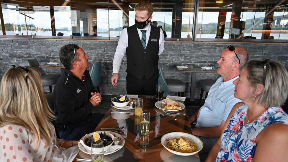 Diners at table, waiter wears mask