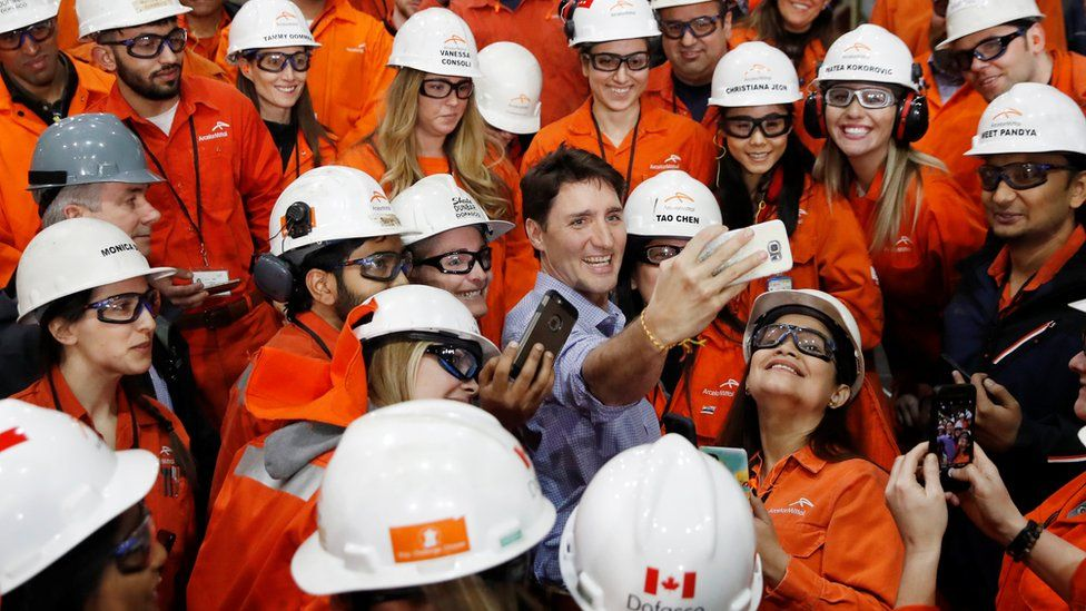 Prime Minister Justin Trudeau takes a selfie with steel workers at a steel plant in Canada