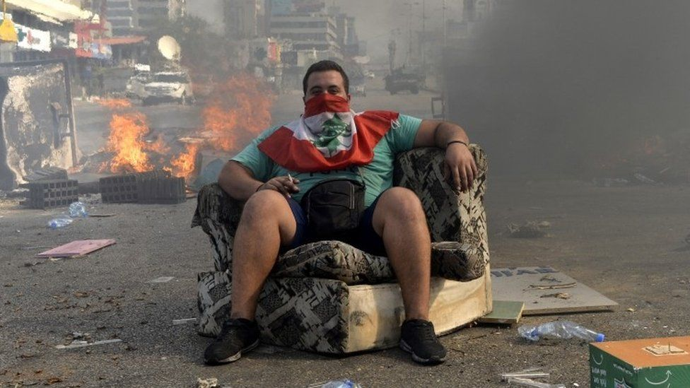 A man sits down in front of flames