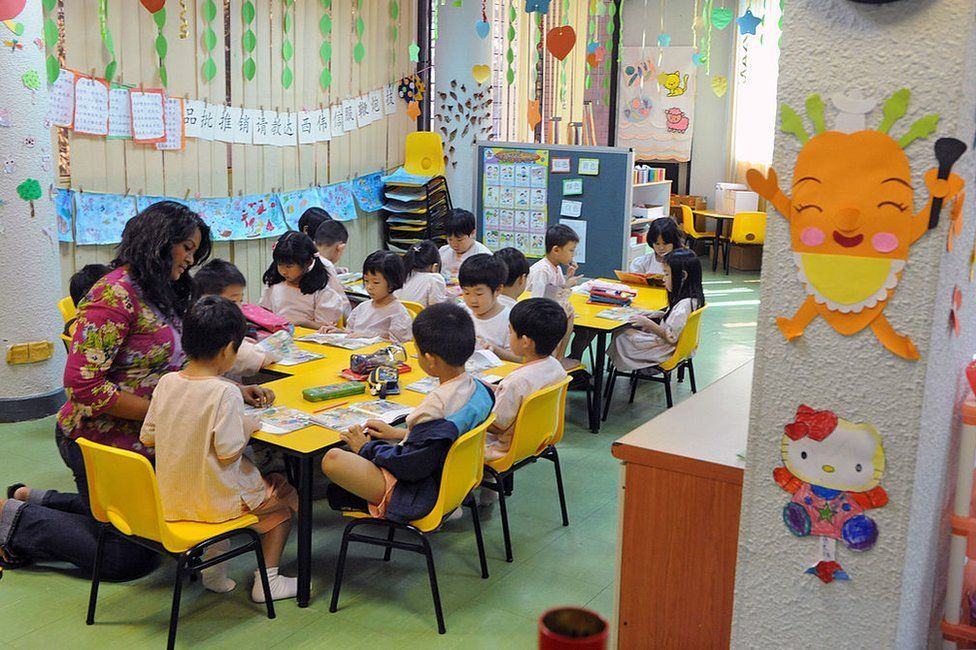 A teacher (L) guides children to read a story book during a lesson in Singapore on 25 May 2010.
