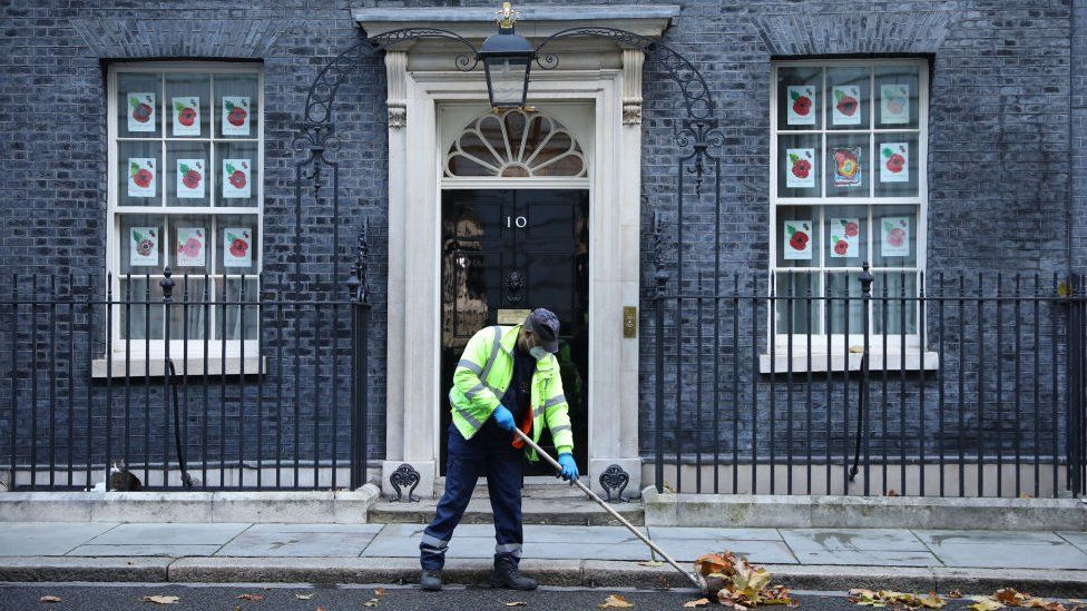 A worker sweeps leaves outside 10 Downing Street