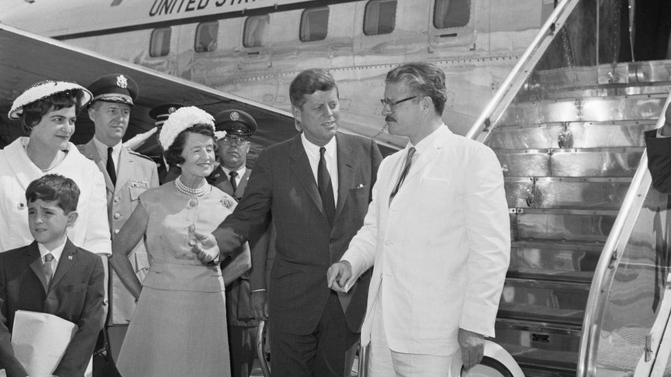 President Kennedy chats with Ecuadorean President Julio Arosemena, (extreme right), as they pose for cameraman at Washington National Airport, July 1962