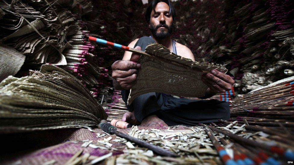 A man makes handmade fans at his workshop in Pakistan, 25 June 2015.