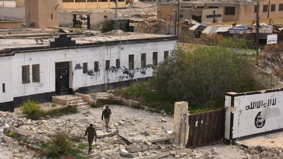 Syrian government forces walk among rubble on 30 March