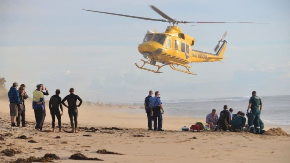 """A photo taken on 31 May, 2016, shows a rescue helicopter arriving to transport a critically injured surfer after a shark ripped off his leg in an attack in Australia""""s west"""