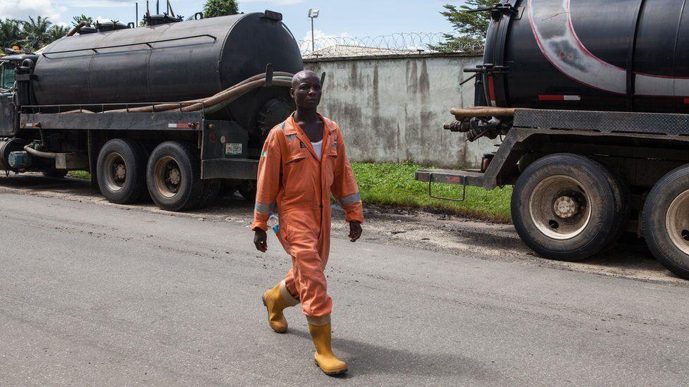 An employee walks past oil trucks at Port Harcourt in Nigeria.