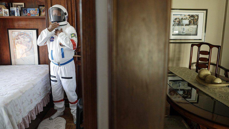 "Tercio Galdino, 66, wears his protective ""space suit"" inside his house"