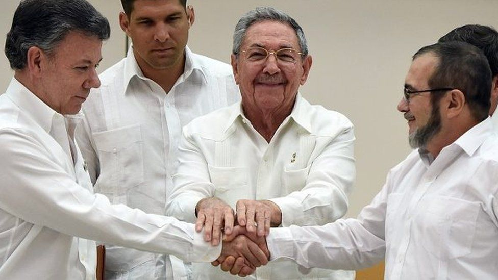 Colombian President Juan Manuel Santos (L) and the head of the FARC guerrilla Timoleon Jimenez, aka Timochenko (R), shake hands as Cuban President Raul Castro (C) holds their hands during a meeting in Havana on September 23, 2015.