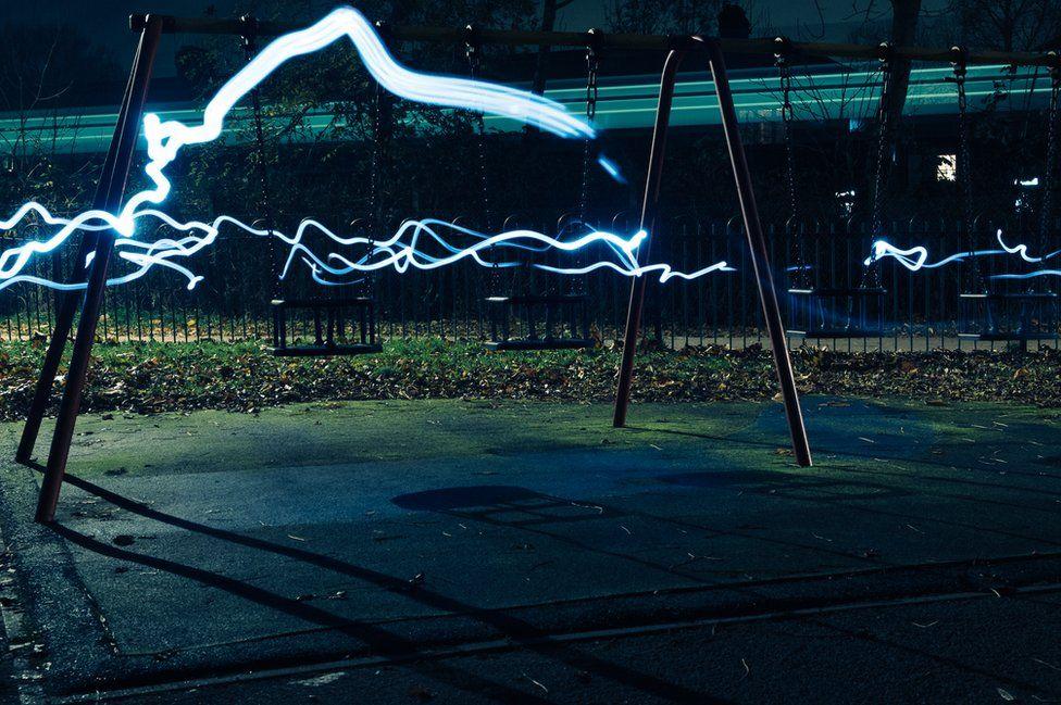 Streams of white light run through an empty playground