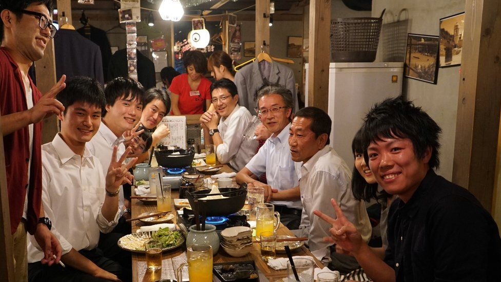 Men sit at a table at an after-work drinking party in Japan