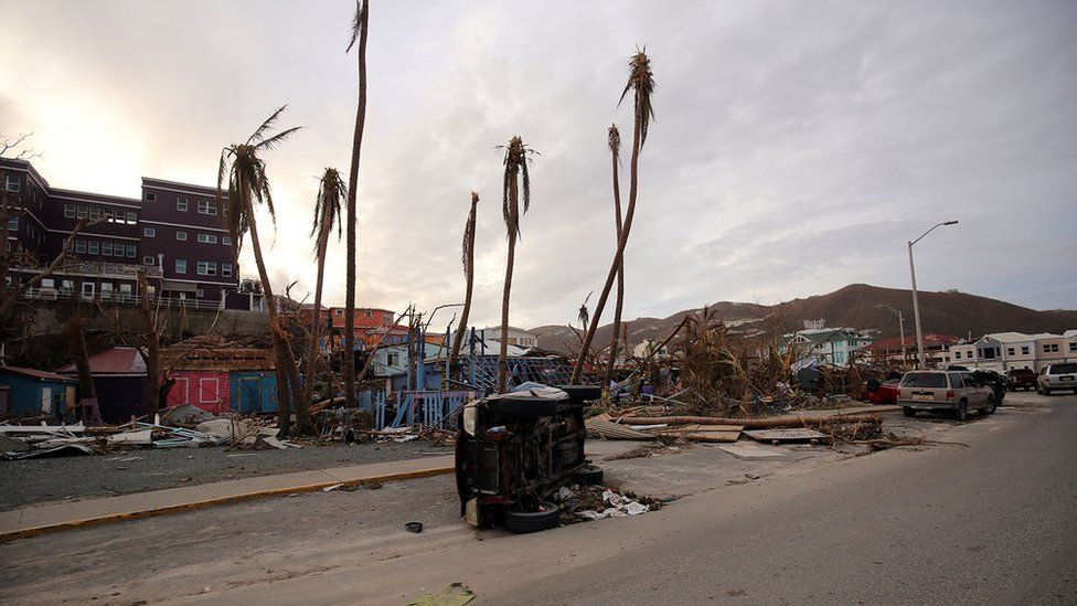 Damaged houses, felled trees and an overturned vehicle on British Virgin Islands