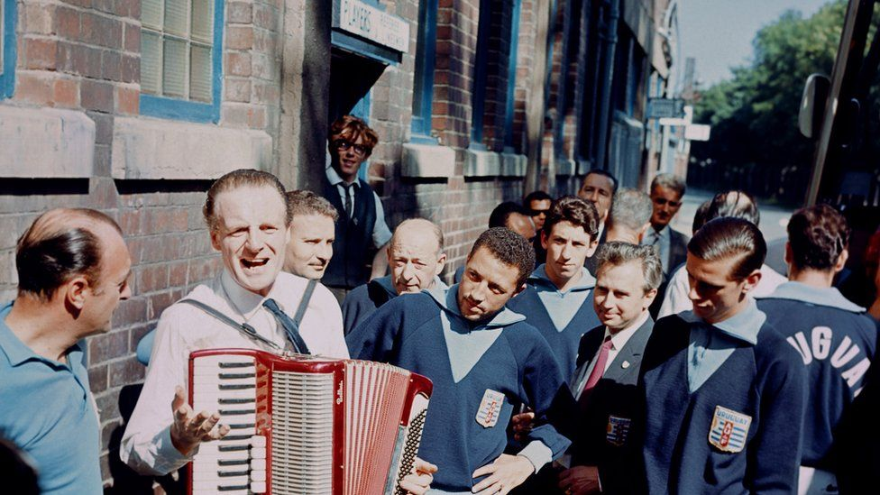 Uruguay's Julio Cortes (centre) and Luis Ramos (right) are intrigued by an accordion player