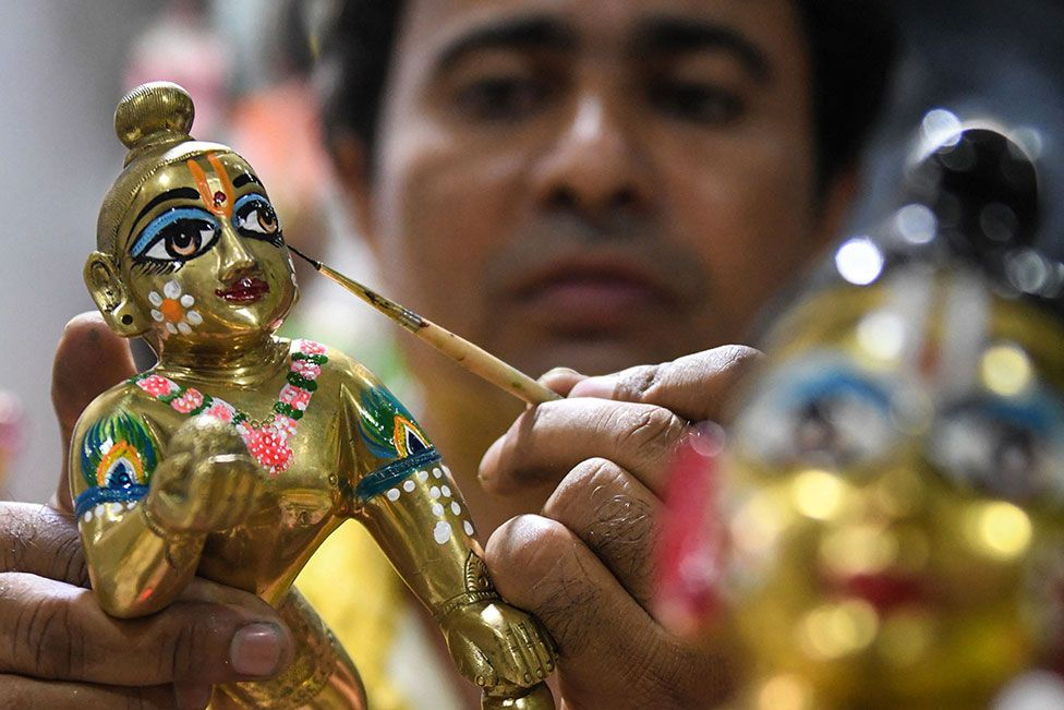 An artist adds the finishing touches to an idol of Hindu deity Lord Krishna
