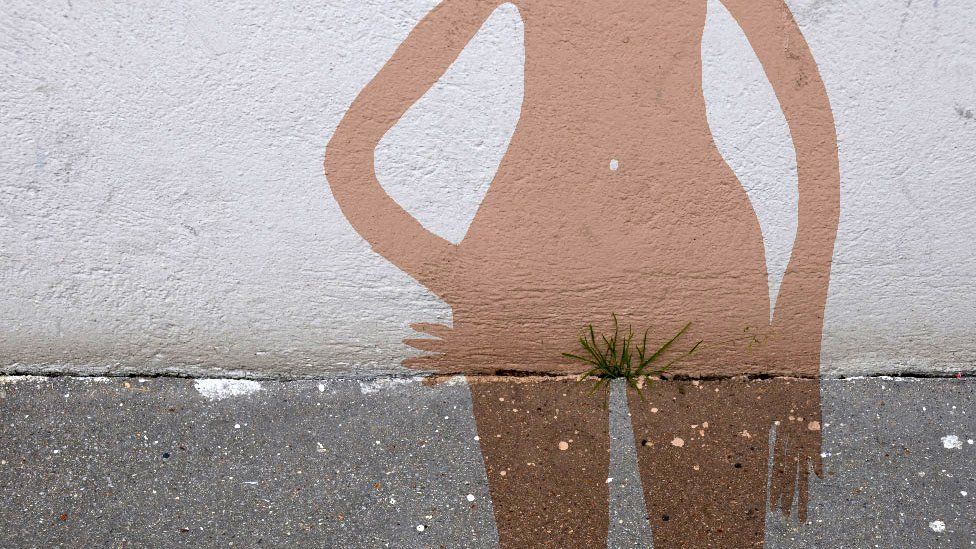 Street art by Sandrine Boulet shows a female contour drawn around grass on a pavement