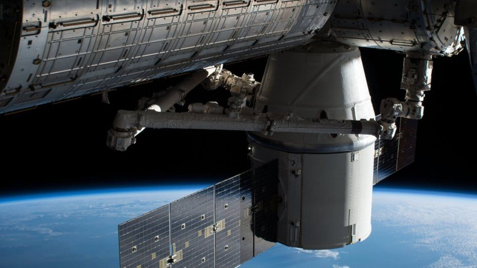Photograph of SpaceX cargo craft attached to the ISS, delivering supplies
