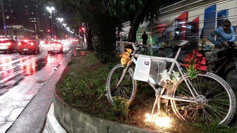 A bike with flowers is left as a memorial to a cyclist who died