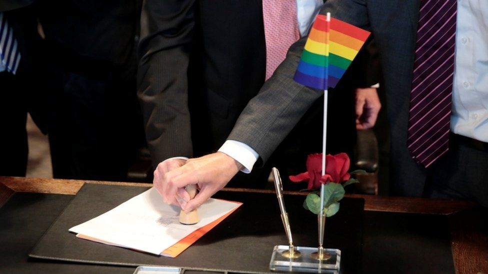 A same-sex couple stamp marriage documents on a desk with a rainbow pride flag on
