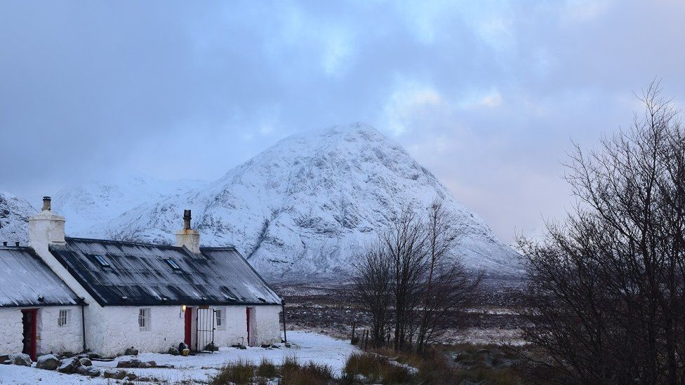 Snow-covered hill with cottage