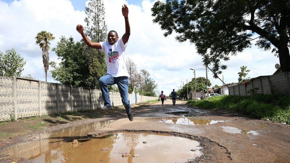 A jumps over a huge pothole full of rain water in what was once a tarred road in the high density suburb of Highfields, Harare, Zimbabwe.