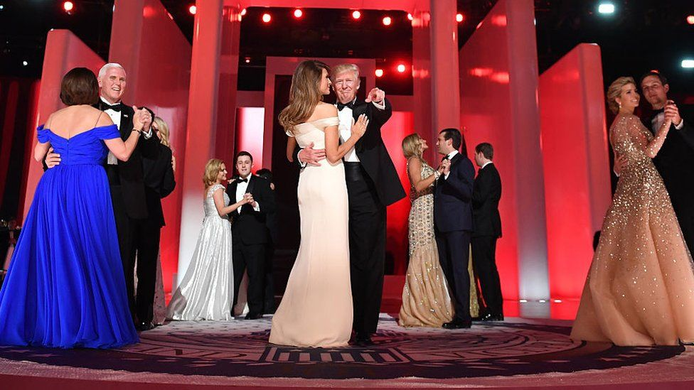 Donald Trump and Melania Trump dance next to other couples at the Inaugural Ball. Mr Trump, in a tuxedo, points towards the crowd.