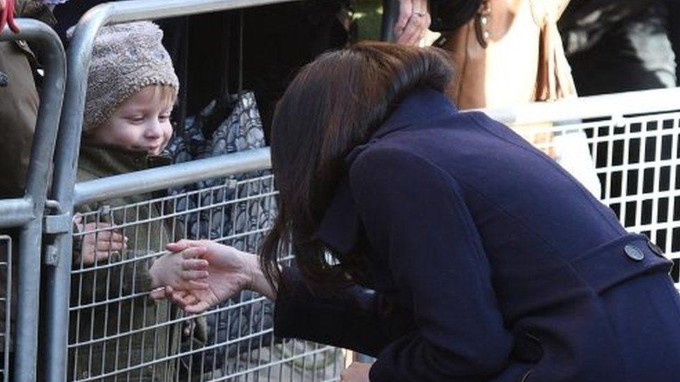 a little boy shakes Meghan Markle's hand