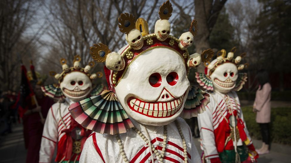 Monks dressed as ghosts take part in the Beating Ghosts ritual in Beijing - the ritual is meant to expel evil spirits