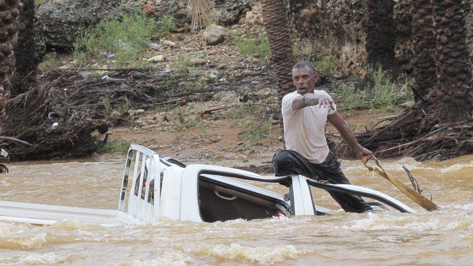 A man tries to save a vehicle from being swept away from water on the Yemeni island of Socotra (2 November 2015)