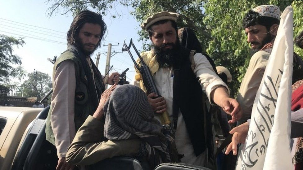 Taliban fighters displaying their flag on outskirts of Kabul on 15 August 2021