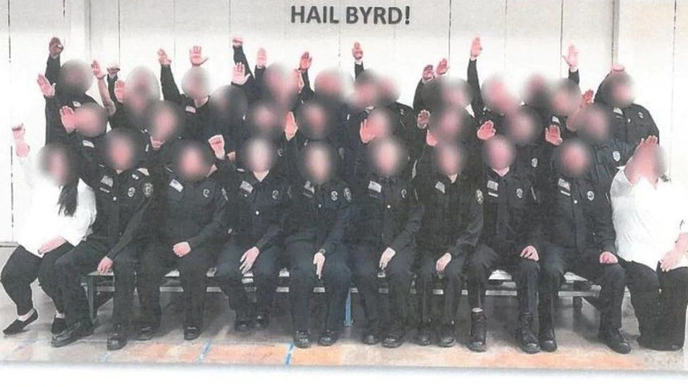 """Employees at the West Virginia Division of Corrections and Rehabilitation giving the salute below a sign that reads """"HAIL BYRD!"""""""