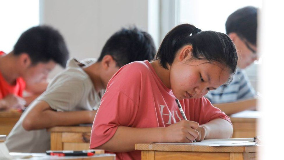 A student takes an exam during the first day of the National College Entrance Examination (NCEE), known as Gaokao