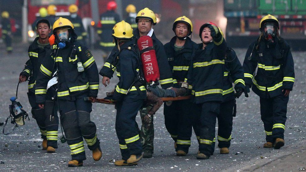 Firemen carry a body at the scene of two powerful explosions in the Chinese city of Tianjin