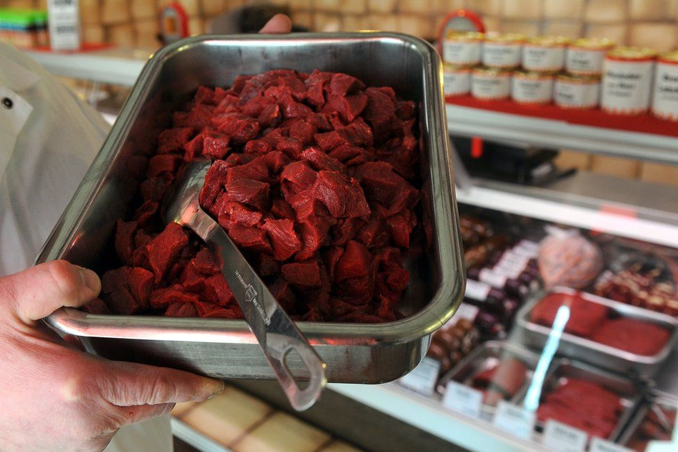 A butcher holds a tray of horsemeat on sale at his shop in Bremen, northern Germany, 14 February 2013
