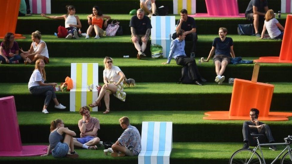 People on the steps near Granary Square in King's Cross, London, as the warm weather continues