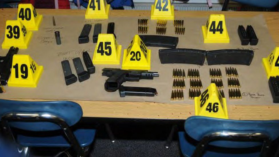Dozens of items of weapons and ammunition are pictured on a table