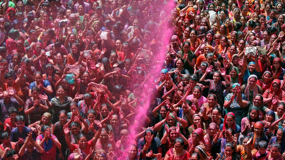 A crowd prays as they are sprayed with colours by a priest