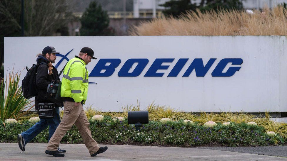 A pair of workers walk past a Boeing sign