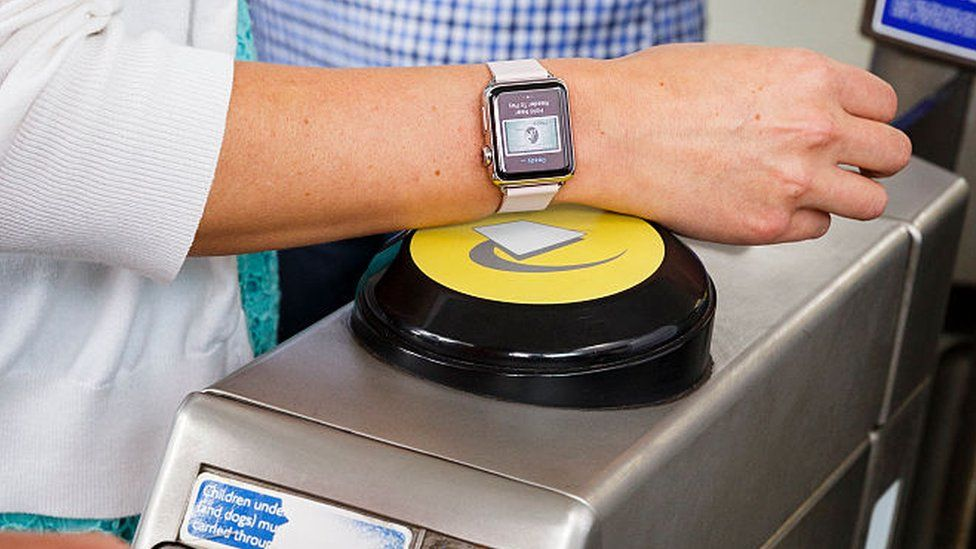 A commuter using their Apple Watch to enter the tube