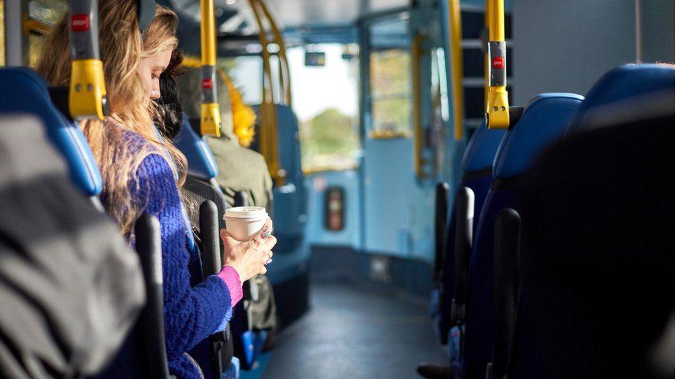 Woman drinking coffee on bus