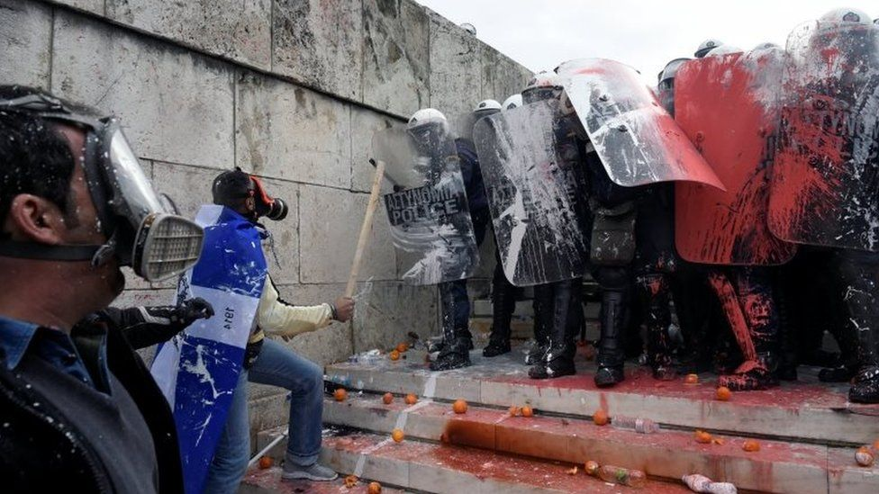 Protestors face off against police who have been doused in paint