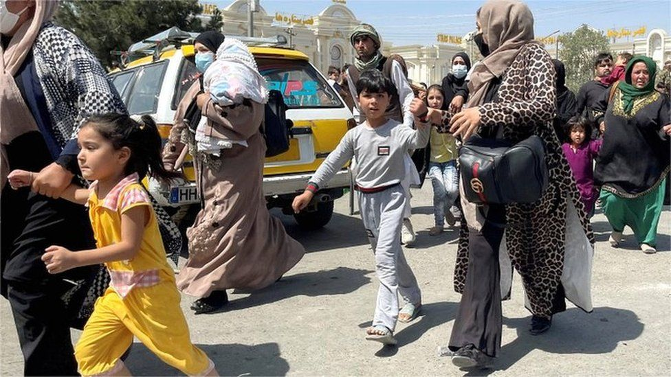 Women with their children try to get inside Hamid Karzai International Airport in Kabul on 16 August 2021