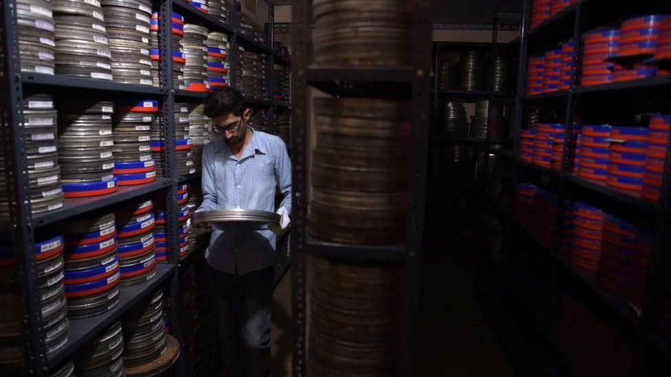 An employee taking a film reel to be digitised at the state-run Afghan Film department in Kabul
